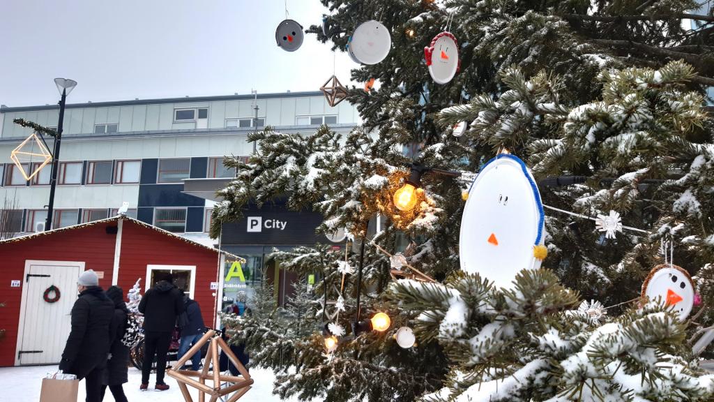 Punainen mökki ja suuri joulukuusi, jonka oksilla on lumiukkokoristeita